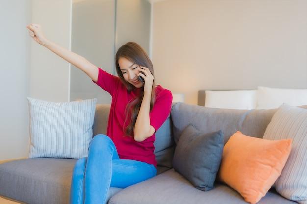 La bella giovane donna asiatica del ritratto utilizza il telefono cellulare astuto sul sofà
