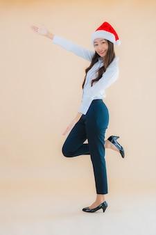 La bella giovane donna asiatica di affari del ritratto indossa il cappello di natale