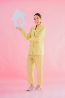 La bella giovane donna asiatica di affari del ritratto mostra il segno della casa o della casa sul colore isolato