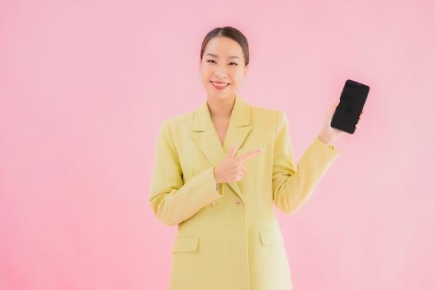 La bella giovane donna asiatica di affari del ritratto usa il telefono cellulare astuto con la tazza di caffè sul colore