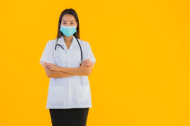 La bella giovane donna asiatica di medico del ritratto con la maschera per protegge covid19