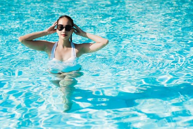La bella giovane donna asiatica felice e sorride nella piscina per si rilassa il viaggio e la vacanza