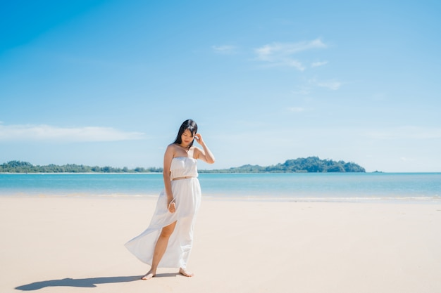 La bella giovane donna asiatica felice si rilassa camminando sulla spiaggia vicino al mare.