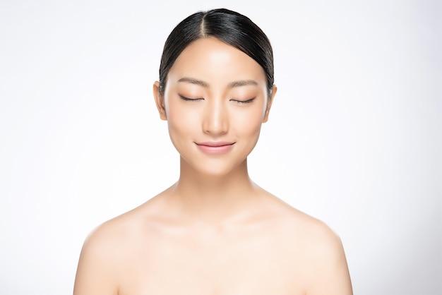 La bella giovane donna asiatica la chiude occhi sorride con pelle pulita e fresca,