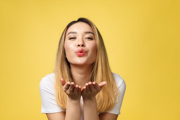 La bella giovane donna asiatica soffia un bacio isolato su fondo giallo