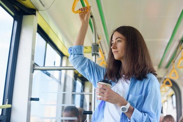 La bella giovane donna beve il caffè delizioso in bus o tram della città. concetto di trasporto pubblico.