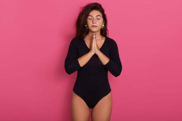 La bella giovane donna caucasica sta nella posa meditativa