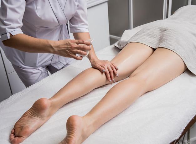 La bella giovane donna che gode delle gambe massaggia con olio nel salone della stazione termale. cosmetologia