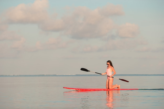 La bella giovane donna che pratica il surfing sopra sta sul bordo di pagaia alla vacanza esotica