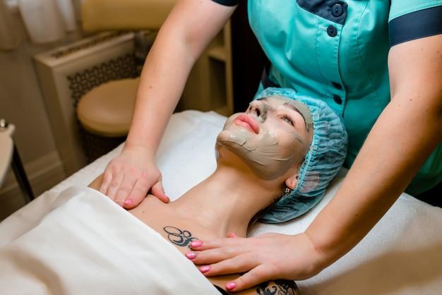 La bella giovane donna che si trova sulla tabella di massaggio mentre la mascherina facciale è messa sul suo fronte.