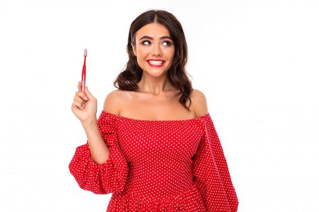 La bella giovane donna con il sorriso e lo spazzolino da denti perfetti consiglia i denti regolari della spazzola, immagine isolata