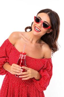 La bella giovane donna con il sorriso perfetto, gli occhiali da sole beve il succo di fragola e guarda da parte, isolato
