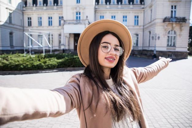 La bella giovane donna con le parentesi graffe fa il selfie durante il giorno soleggiato