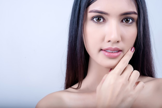La bella giovane donna con pelle pulita fresca distoglie lo sguardo