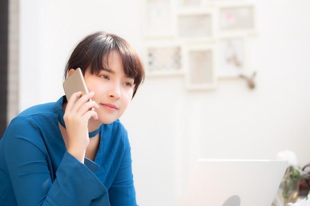 La bella giovane donna di affari asiatica ha eccitato e felice del lavoro di successo con il computer portatile