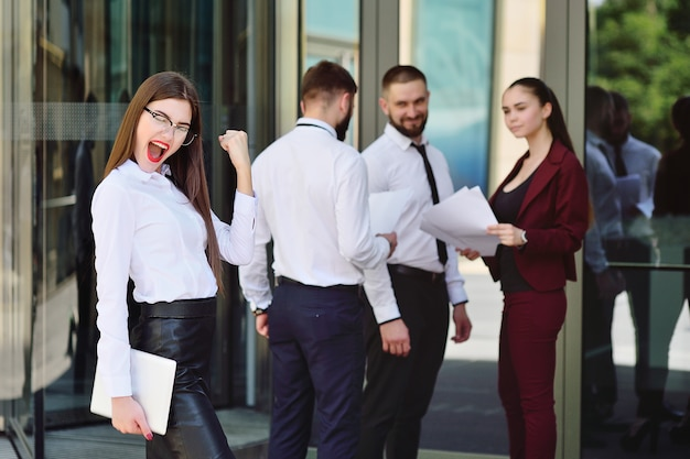 La bella giovane donna di affari è felice contro la superficie di un edificio per uffici e colleghi o colleghi. successo negli affari. carriera. vacanza tanto attesa
