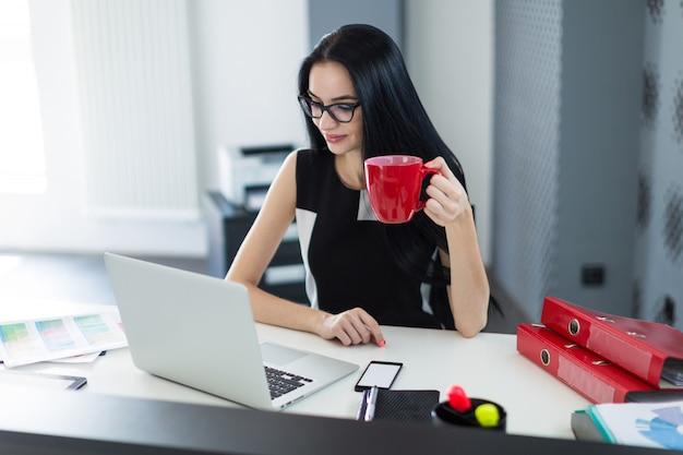 La bella giovane donna di affari in vestito e vetri neri si siede alla tavola e lavora con il caffè a disposizione
