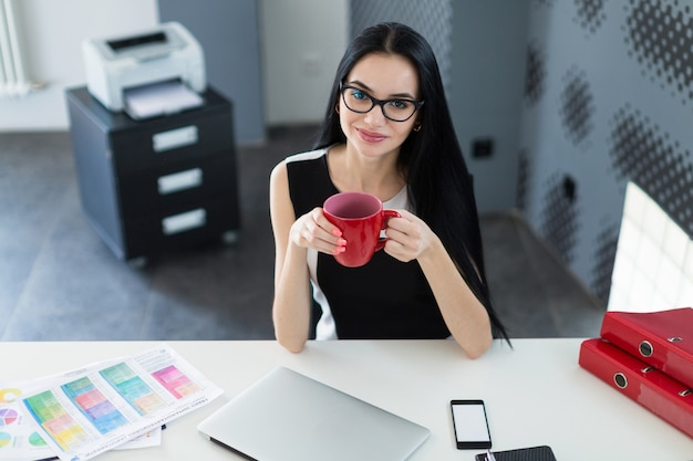 La bella giovane donna di affari in vestito e vetri neri si siede alla tavola e tiene la tazza rossa