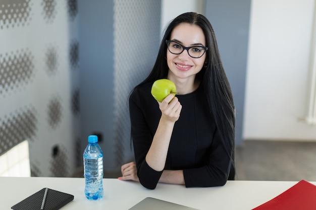 La bella giovane donna di affari in vestito e vetri neri si siede sulla tavola nell'ufficio e tiene la mela verde