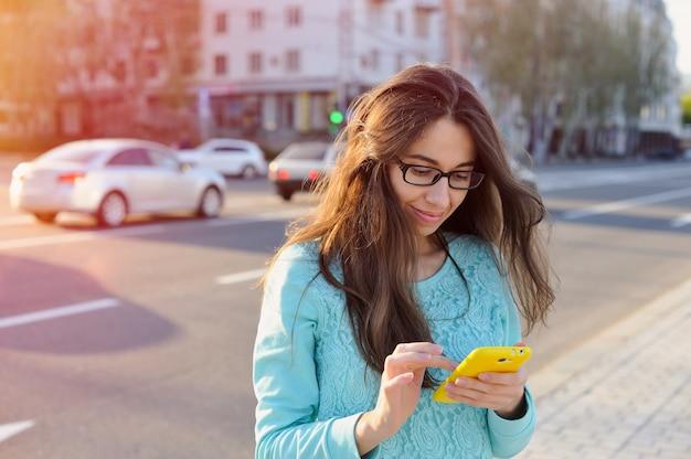 La bella giovane donna di affari scrive sullo smartphone