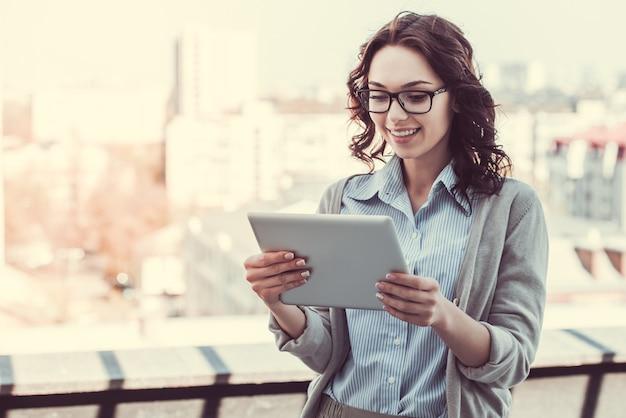 La bella giovane donna di affari sta usando una compressa digitale.