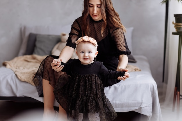 La bella giovane donna e la sua piccola figlia affascinante stanno abbracciando e sorridendo sul letto