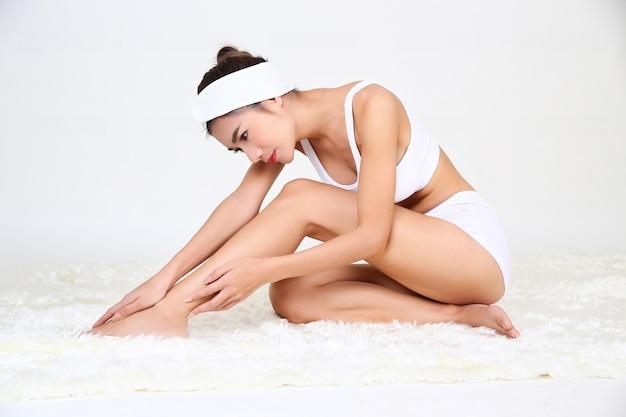 La bella giovane donna esile sta trattando i suoi piedi