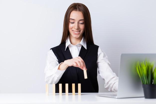 La bella giovane donna fa i cubi di legno sulla scrivania in ufficio