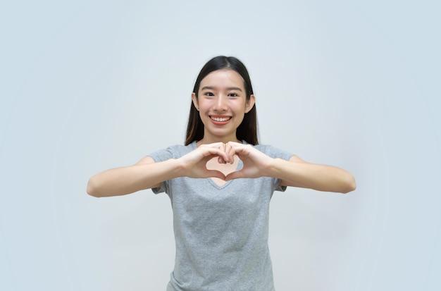 La bella giovane donna fa il simbolo del cuore a mano, ritratto, ragazza asiatica