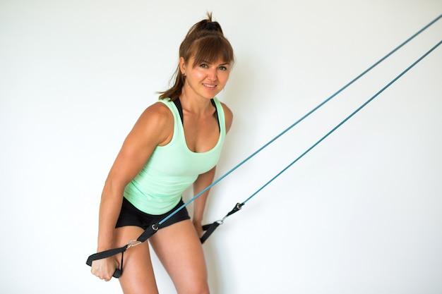 La bella giovane donna fa sport a casa
