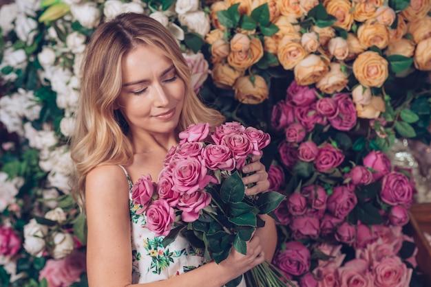 La bella giovane donna fresca che tiene il mazzo di rosa a disposizione