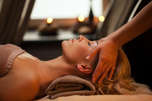 La bella giovane donna gode del massaggio