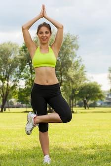 La bella giovane donna gode dell'yoga in un parco
