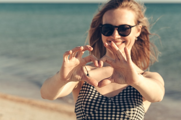 La bella giovane donna gode delle vacanze estive sulla spiaggia