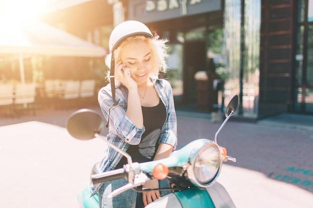 La bella giovane donna ha vestito la seduta casuale sul motorino e sulla conversazione sul telefono