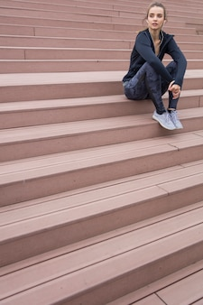 La bella giovane donna in abiti sportivi e con le cuffie che distoglie lo sguardo mentre riposano sulle scale durante la mattina funziona