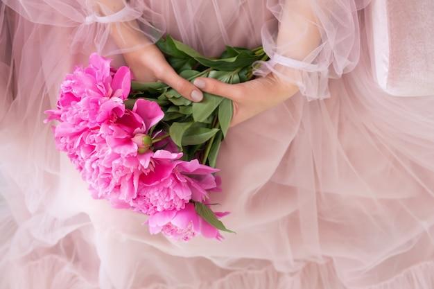 La bella giovane donna in vestito rosa che tiene la peonia fiorisce il mazzo in sue mani