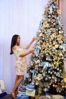 La bella giovane donna incinta decora un albero di natale