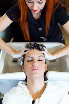 La bella giovane donna lava i capelli in un salone di bellezza.