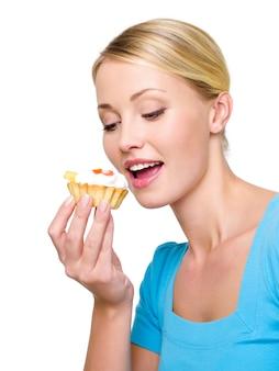 La bella giovane donna mangia la torta dolce con crema bianca