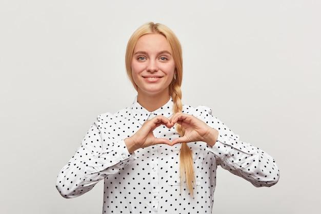 La bella giovane donna mostra l'emozione su una priorità bassa bianca. la ragazza mostra il gesto di forma del cuore