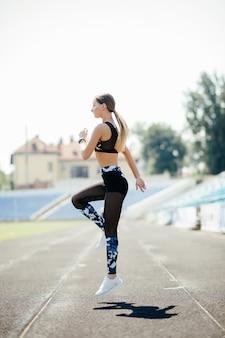 La bella giovane donna nell'abbigliamento di sport che riscalda con il salto si esercita mentre si esercita all'aperto.