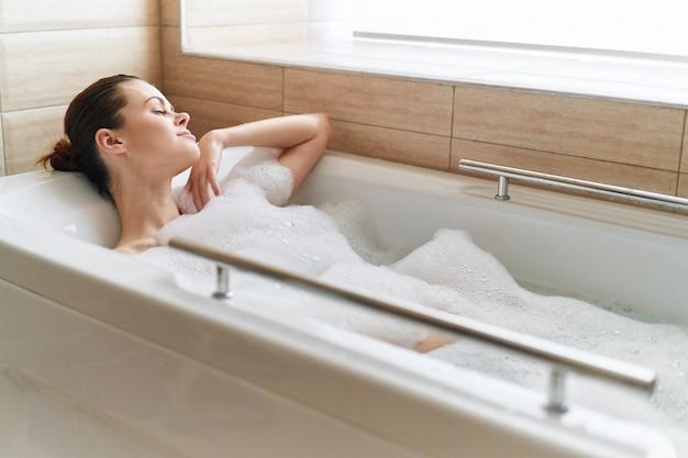 La bella giovane donna nella sua bella vasca bianca come la neve riposa e rilassa, bella prova, vasca da bagno con schiuma