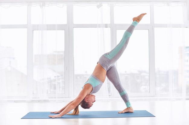 La bella giovane donna pratica lo yoga asana eka pada adho mukha shvanasana