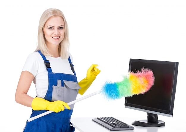 La bella giovane donna pulisce l'ufficio.