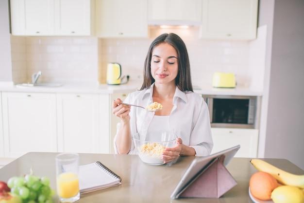 La bella giovane donna si siede al tavolo e mangia latte con fiocchi di mais.