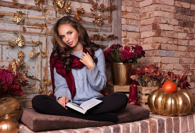 La bella giovane donna si siede con un libro nell'interno di autunno.