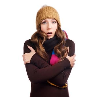 La bella giovane donna sorpresa si è vestita con i vestiti dell'inverno, isolato su bianco