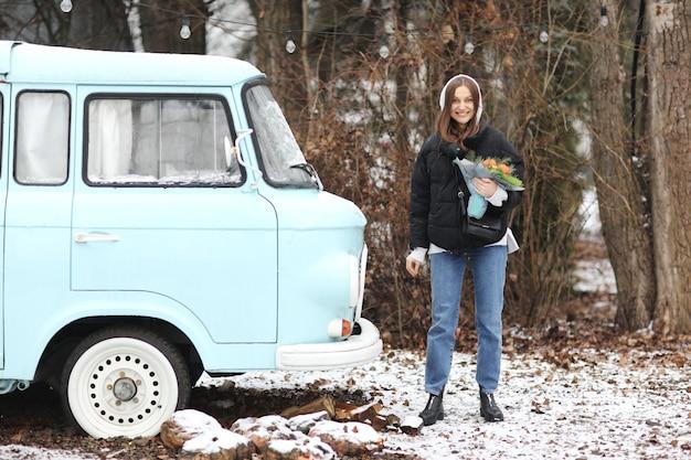 La bella giovane donna sta divertendosi vicino alla retro automobile blu nel parco dell'inverno. ragazza che tiene un mazzo di mandarini e abete rosso fatto con le sue mani.