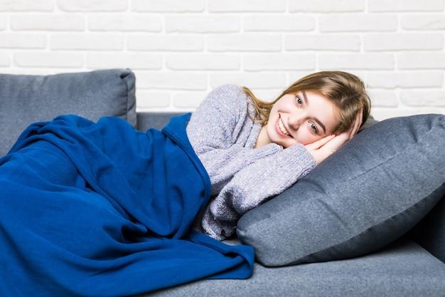 La bella giovane donna sta dormendo e sta vedendo dolci sogni nel divano